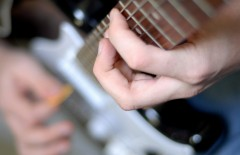 hands on frets of guitar with shallow depth of field