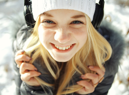 Winter portrait of young girl with headphones music