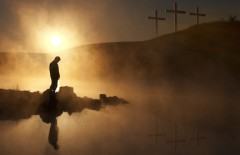 Three Crosses and Silhoutted Person in Prayer at Sunrise