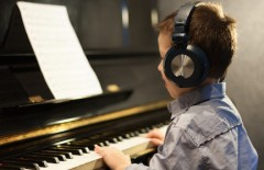 Boy listening to music and learning piano