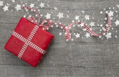 Present wrapped in red paper on a wooden background for a voucher or a christmas or birthday greeting card