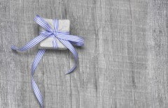 Giftboxes with blue striped ribbon on a wooden background